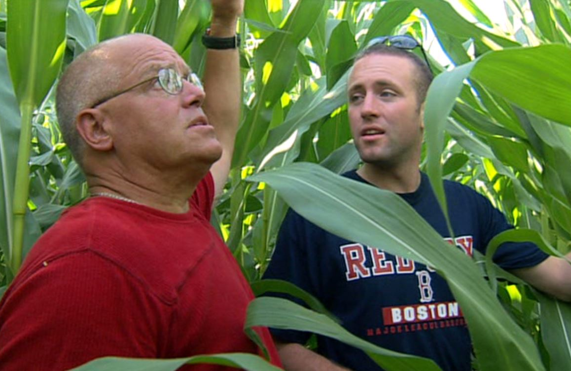 With an assist from his uncle Bruce, Ian Cheney inspects his summer crop in this image from <i>King Corn</i>.