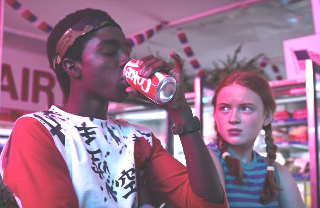 Max Mayfield (Sadie Sink) looks on as Lucas Sinclair (Caleb McLaughlin) enjoys the clean crisp taste of New Coke in Stranger Things 3. (Netflix)