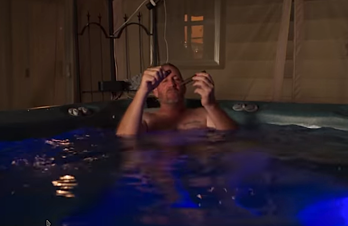 "<i>Relaxing alone in a hot tub, Coach Brown brags, ""I believe I'm the best recruiter in America."" (Netflix)</i>"