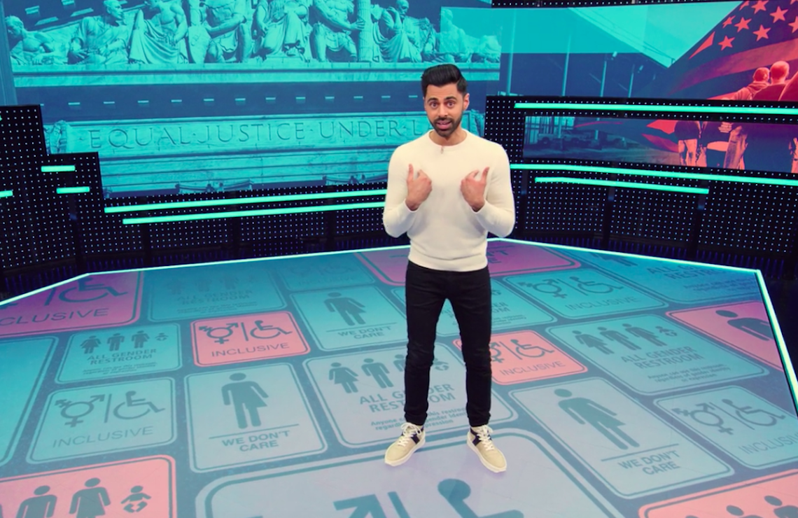 Hasan Minhaj on the set of Patriot Act, which features a wraparound video wall and floor with a fast-moving parade of infographics, images, and source notes. (Netflix)