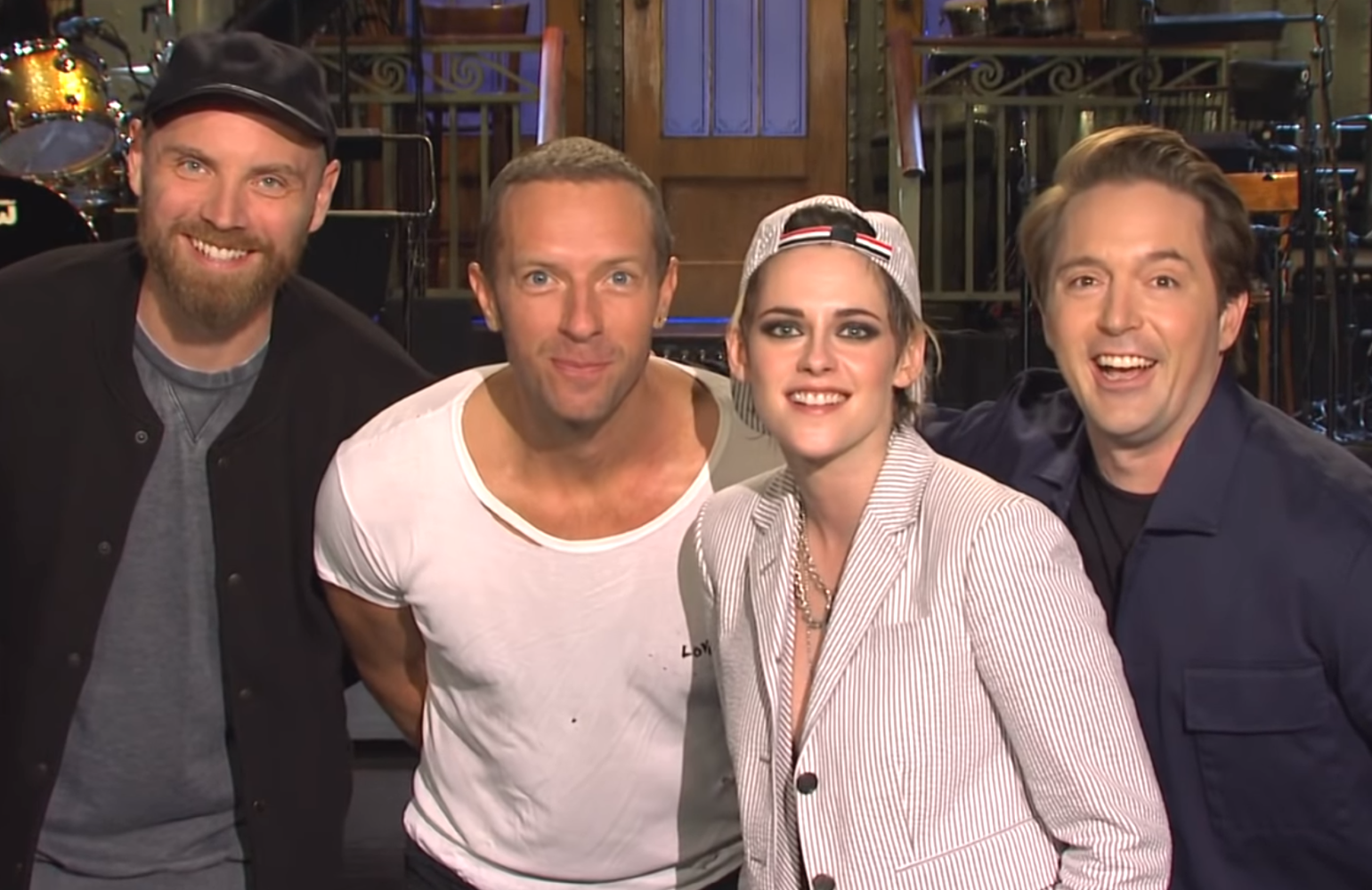 SNL host Kristen Stewart strikes a pose with musical guest Coldplay and Beck Bennett. (NBC)