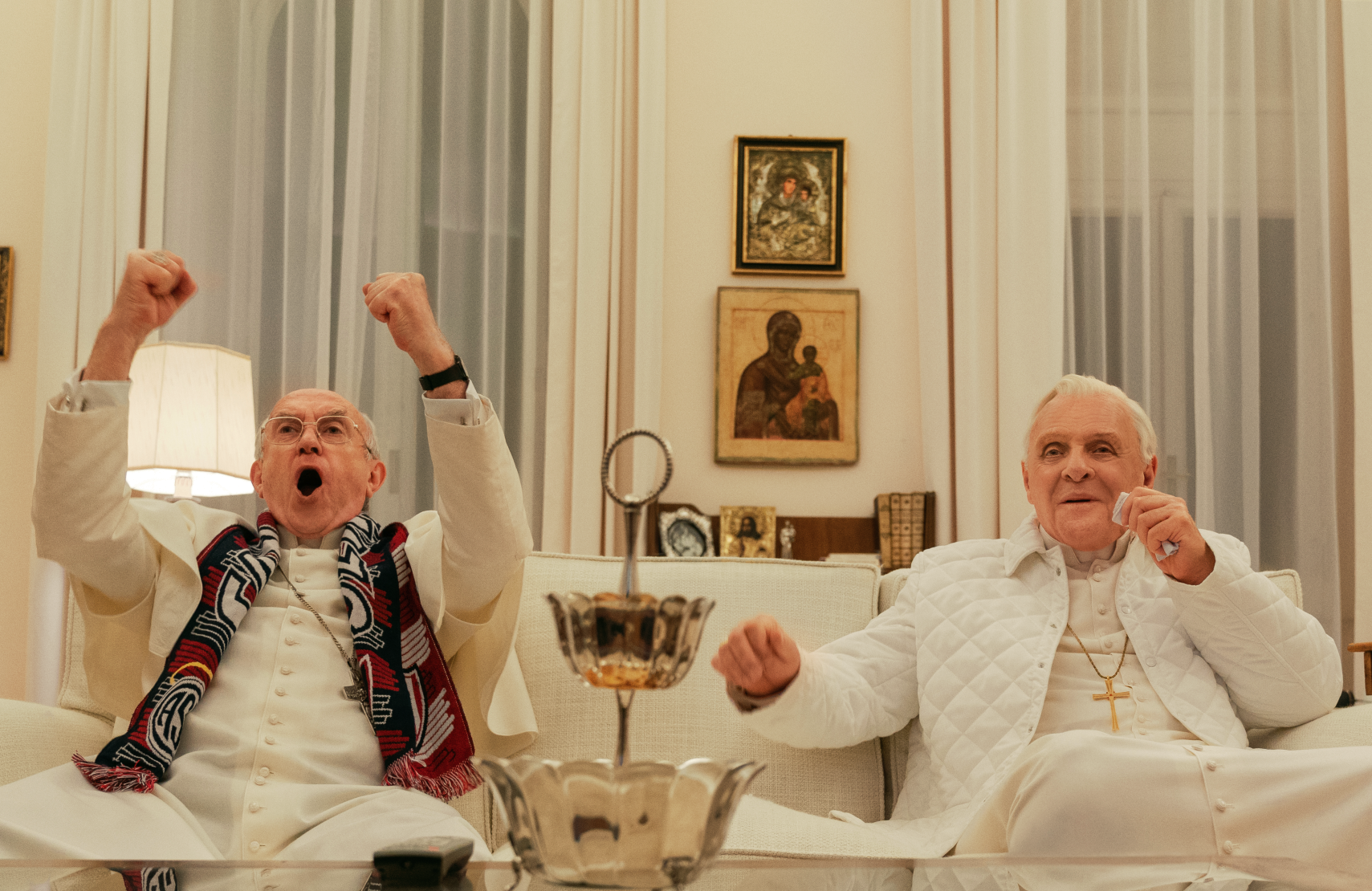 Cardinal Bergoglio (Jonathan Pryce) and Pope Benedict (Anthony Hopkins) take a break from debating the church's future to enjoy some sport on TV. (Netflix)