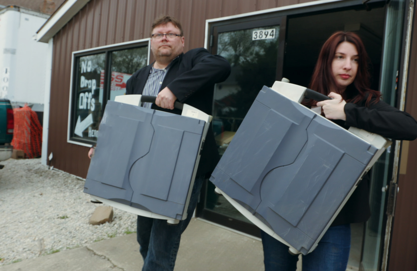 Harri Hursti and Maggie MacAlpine carry voting machines they purchased in an image from Kill Chain (Photo: HBO)