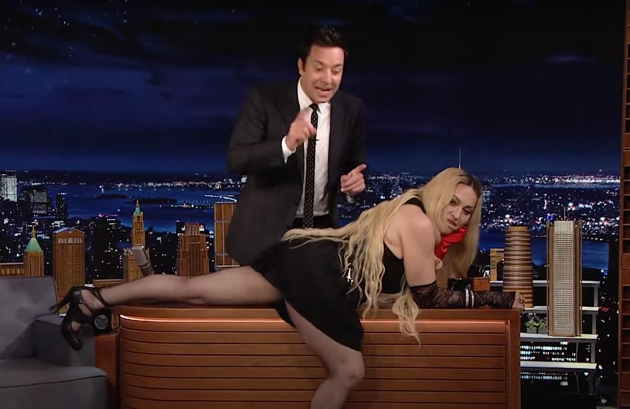 Madonna lays across Jimmy Fallon's desk on The Tonight Show (Photo: NBC)