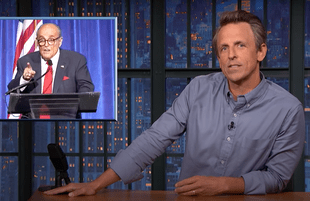 Seth Meyers next to a graphic of Rudy Giuliani giving a speech at a 9/11 dinner (Photo: NBC)
